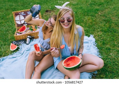 Two beautiful girls eating watermelon for a picnic