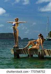Two beautiful girls in fashionable bikinis enjoying summer time at tropical island. Sunbathing and posing on the pier.