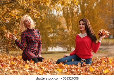 Two beautiful girls friends in autumn park
