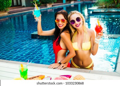 two beautiful girls friends bassen on the hotel water background. Dressed in red yellow swimsuits in the hands of bright refreshing cocktails and sunglasses. Summer vacation sexy smile having fun