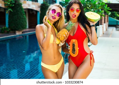 Two beautiful girls friends bassen on the hotel water background. Dressed in swimwear red yellow in hands fruit pineapple watermelon sunglasses. Summer vacation sexy smile having fun