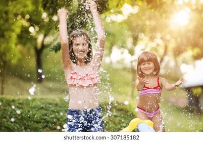 Two beautiful girls having fun outside in the garden