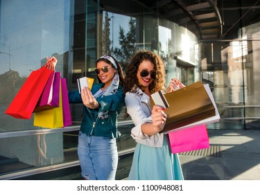 Two beautiful girls holding credit cards in front of the camera , shopping bags and smiling