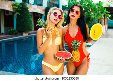 Two beautiful girls ladys friends bassen on the hotel water background. Dressed in swimwear red yellow in hands fruit pineapple watermelon sunglasses. Summer vacation sexy smile having fun