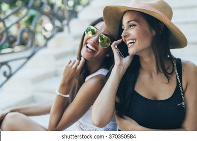 Two beautiful girls laughing while talking on phone with a boy