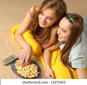 Two beautiful girls look cinema laying on a carpet