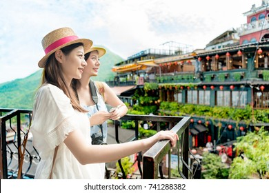 two beautiful girls looking at famous landmarks Amei tea house views of Jiufen Taipei Taiwan. Travel holiday vacation concept.
