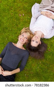 Two beautiful girls lying in the grass and laughing.
