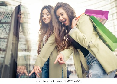 Two beautiful girls making shopping in the city center. Indicating clothes in a shop window