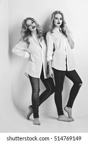 Two beautiful girls in men shirts and jeans
