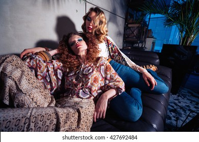 Two beautiful girls models poses for the camera. Furnishings, clothing and design in the style of the 70s.