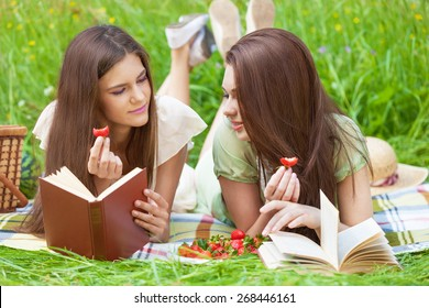 Two beautiful girls on picnic eating strawberry while reading books