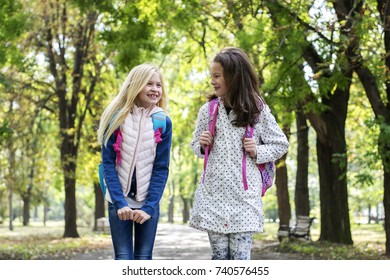 Two beautiful girls  in park are going to school