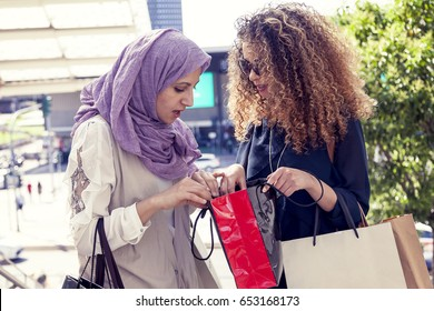 two beautiful girls with shopping bags walk up stairs in the heart of the city