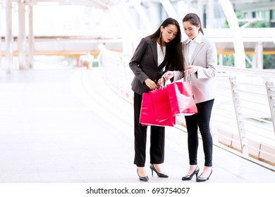 Two beautiful girls shopping together. Asian woman and white girl smartly dress going out shopping during lunch time in work days. Taken outdoor with natural lights in business district walk way.