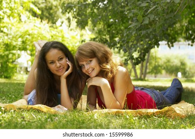 two beautiful girls sit in park