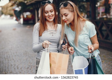 Two beautiful girls in a summer city. Ladies with shopping bags
