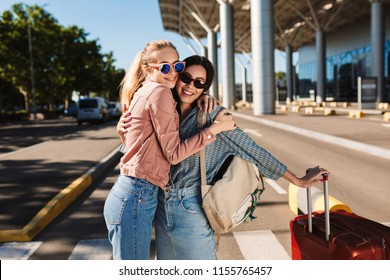 Two beautiful girls in sunglasses happily hugging each other looking in camera with red suitcase and backpack on shoulder outdoor near airport