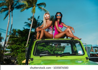 two beautiful girls in swimsuits and sunglasses travel on an SUV, an off road car on a tropical island, a summer trip, a fashionable photo