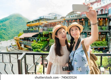 two beautiful girls taking selfie photo of famous landmarks Amei tea house of Jiufen Taiwan. Travel holiday vacation concept.