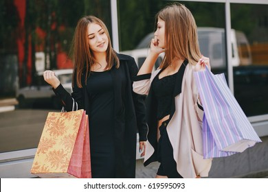 Two beautiful girls walking with large bags and shopping