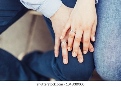 Two beautiful hands of married couple holding hands together with rings
