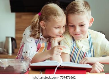 Two beautiful and happy children having fun exploring receipt before preparing christmas cookies