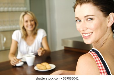 Two beautiful happy girls having coffee and desserts together
