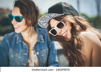 Two beautiful happy girls in sunglasses on the urban background. Young active people. Outdoors