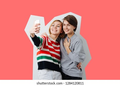 Two beautiful happy and smiling young women with short hair, warmly dressed, hugging as best friends, coral background scissors-like clipping. Open smiles. Taking selfie.