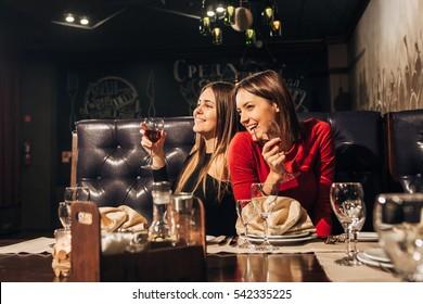 Two beautiful happy women having fun in a bar drinking wine