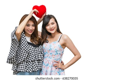 Two beautiful happy women holding red heart on a white background.