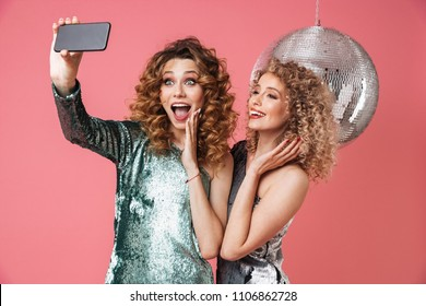 426f2bf09d4 Two beautiful happy women in shiny dresses taking a selfie while standing  with disco ball isolated