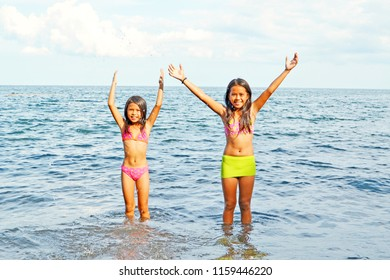 Two beautiful happy young girls playing with the water in the sea during summer day with much fun