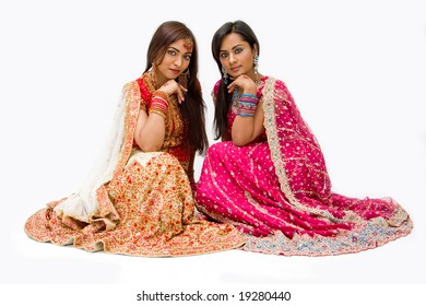 Two beautiful harem girls or belly dancers or Hindu brides sitting, isolated