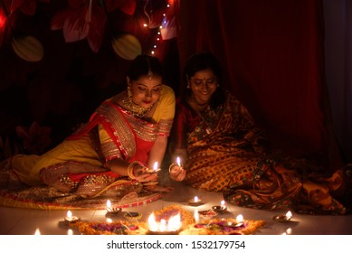 Two beautiful Indian Bengali women in Indian traditional dress lightening Diwali diya/lamps sitting on the floor indoor in darkness on Diwali evening. Indian lifestyle and Diwali celebration