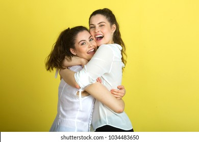 two beautiful joyful sisters sister girls in white blouses on a yellow background hugging each other