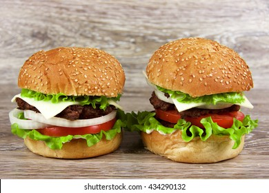 two beautiful juicy hamburger on a wooden table