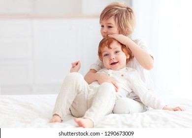 two beautiful kids, brothers cuddling, playing together at home
