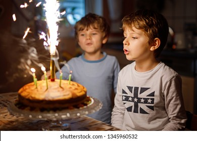 Two beautiful kids, little preschool boys celebrating birthday and blowing candles on homemade baked cake, indoor. Birthday party for siblings children. Happy twins about gifts and fireworks on tarte
