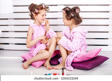 Two beautiful kids play cosmetics. Beauty salon. The concept is childhood, fashion, beauty, lifestyle.