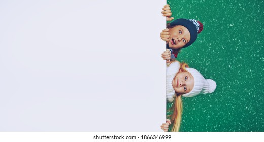 Two beautiful kids in winter clothes look out from behind the white board and are smiling. Green background with snowfall. Winter fashion, winter activities. Christmas and New Year. Copy space.