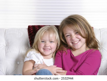 two beautiful litlle girls on white background smiling