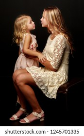 Two beautiful little girls with flowers in the studio. The concept of happy people, children.