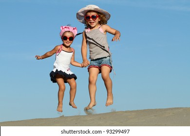 Two beautiful little girls jumping on the sand