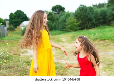 Two beautiful little girls playing and smiling at sunny summer day outdoors. Happy childhood concept