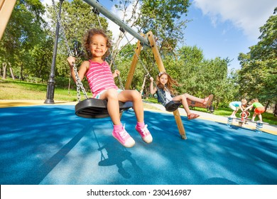 Two beautiful little girls swinging on swings on playground with smile on sunny summer day
