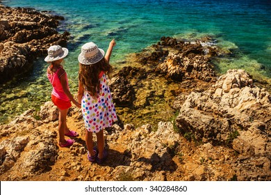 Two beautiful little sisters on the rocky shores of the Adriatic Sea in Croatia.