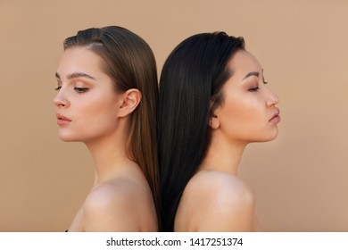 Two beautiful multicultural young women hugging while posing camera over beige background