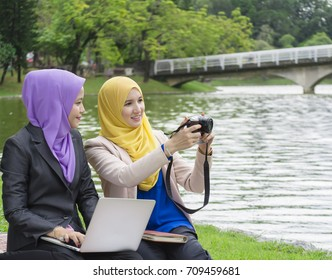 Two beautiful muslim women are discussing and taking picture at public park
